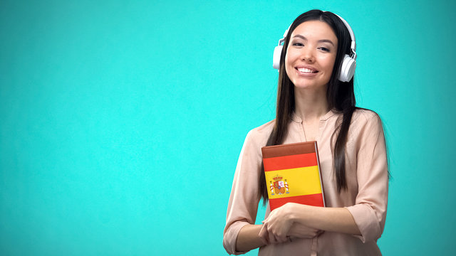 Girl listening Spanish audio lessons in headset, book in hands, translations