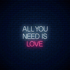 All you need is love - glowing neon inscription phrase on dark brick wall background. Motivation quote in neon style