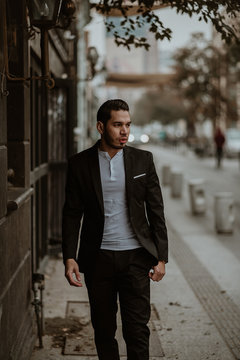 Elegant man walking on sidewalk