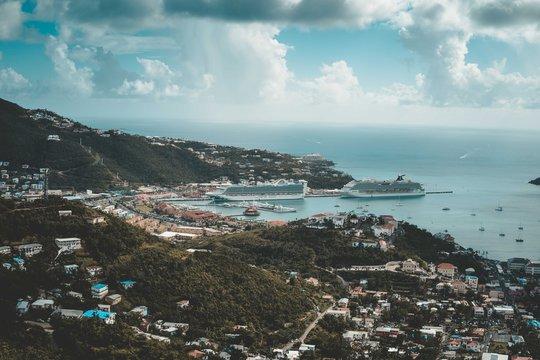 large cruise ships sit in ocean harbor