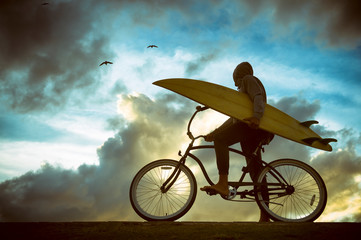 Silhouette of surfer carrying his surfboard on a beach cruiser bike in front of bright skyscape