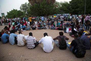 Sudanese protesters read from the Koran during a silent demonstration as a memorial to lost colleagues at the sit-in protest near the military headquarters in Khartoum