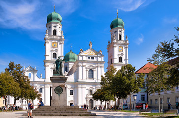 St. Stephens Basilica is an old white church with green metal domes on top of the towers in Passau, Germany. In front of the Church is a statue of Maximillian Joseph Wall mural