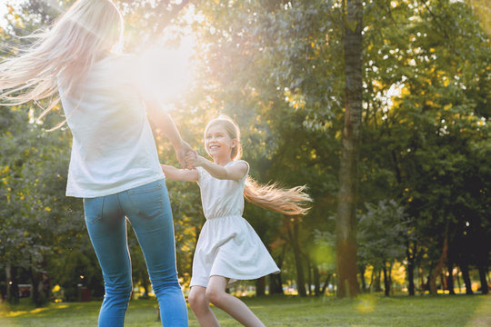 Mother and little daughter dancing, having fun in a park
