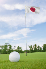 Japan flag on golf course putting green with a ball near the hole