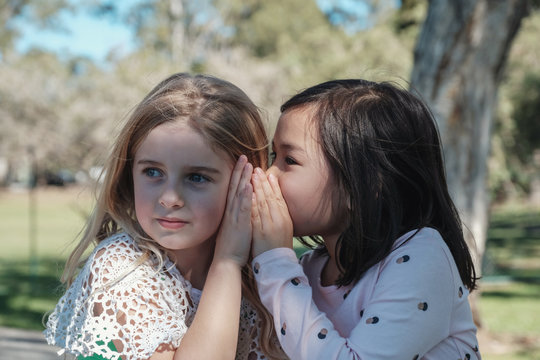 multiethnic young little girls playing kids Chinese whispering  in the park, best friends and positive friendship concept