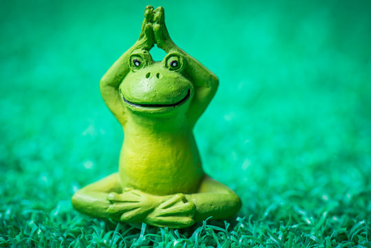 Cute little wooden frog doing yoga poses on a green grass like mat.