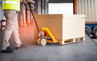 warehouse worker with hand pallet truck unloading goods pallet into a truck. Wall mural