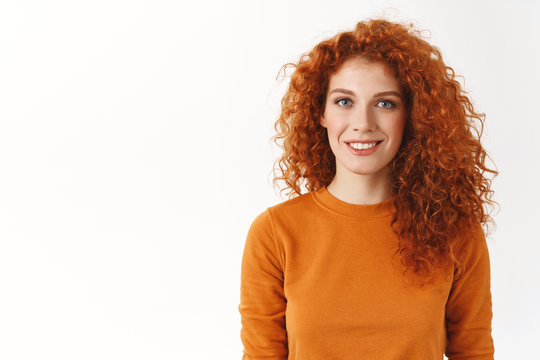 Happy cute redhead woman with curly hair smiling sincere and carefree, standing white background wear orange sweater, look camera normal casual attitude, customer support answer questions politely