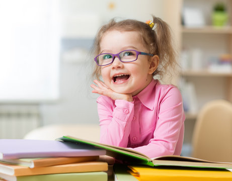 Smart kid girl in eye glasses reading books in her room