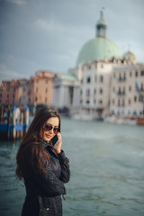 girl talking on the phone and taking pictures in Venice Italy