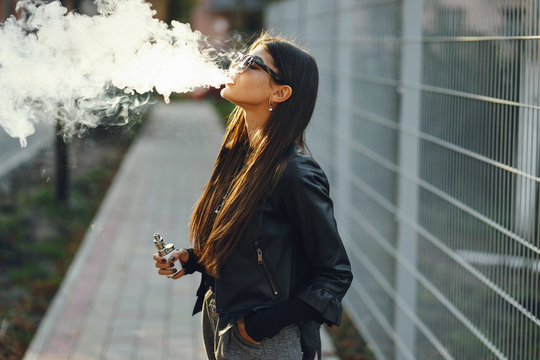 stylish girl smoking an e-cigarette as she is walking through the city