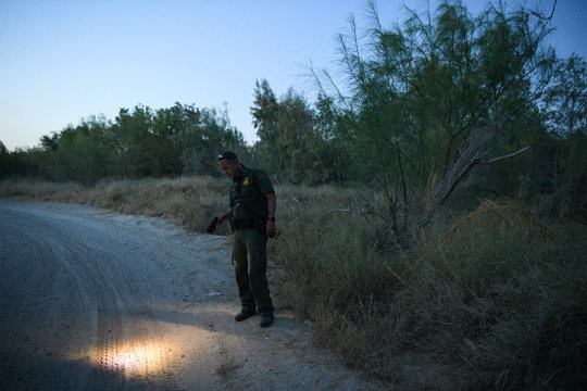 A U.S. Border Patrol agent looks for migrant shoe prints by an illegal crossing area on the Rio Grande near Mission