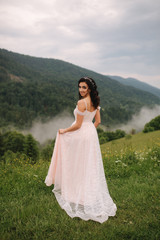 Charming bride in beautiful Carpathian mountais. Elegant woman in beautiful dress