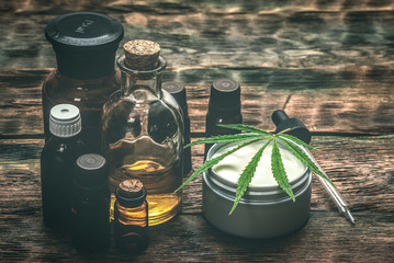 Cannabis face cream or moisturizer jar and cbd oil bottles concept.