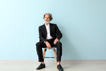Fashionable senior man sitting on chair near color wall Wall mural