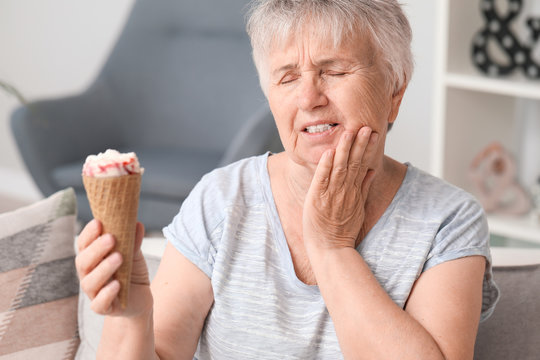 Senior woman with sensitive teeth and cold ice-cream at home