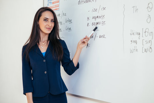 Teacher near whiteboard explains the rules. Learn foreign language.