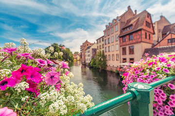 Poster Salmon Colorful and fabulous landscape with decorative flowers and the river Ill and half-timbered houses in Strasbourg, France