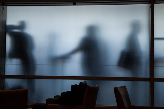 smokers in an airport behind a frosted glass