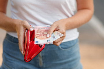 Female hands gets money from the wallet. Euro cash background.