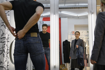 Keuken foto achterwand Fitness Girl seller helps a man to choose clothes in the store