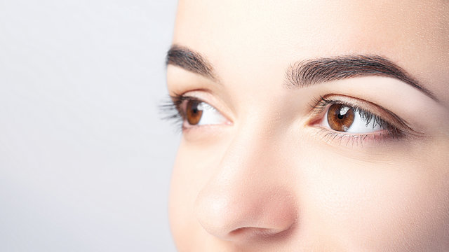 Woman with beautiful eyebrows close-up on a light background with copy space. Microblading, microshading, eyebrow tattoo, henna, powder brows concept