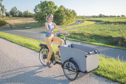 Frau fährt mit Lastenrad, E-Mobilität