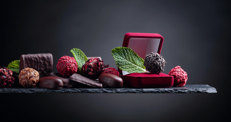 Various chocolates with mint leaves on a black background.