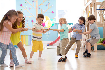 Group of kids play and pull rope together in daycare. Games in kindergarten Wall mural