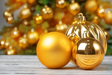 Christmas baubles on wooden table against decorated christmas tree blurred background Wall mural