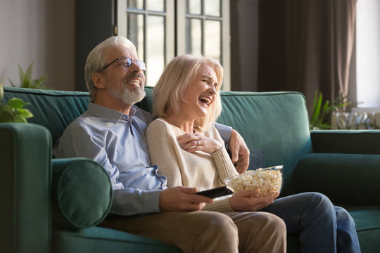 Cheerful old couple holding remote control laughing watching funny tv