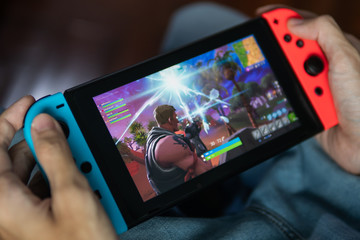 Bangkok, Thailand - July 30, 2018 : Gamer playing Fortnite game on Nintendo Switch.