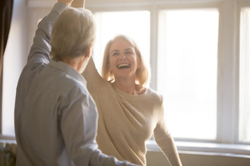 Happy middle aged mature woman enjoying dancing with elder husband