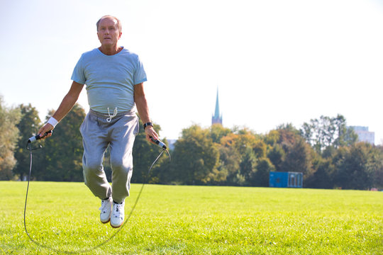Determined senior man working out with skipping rope in park