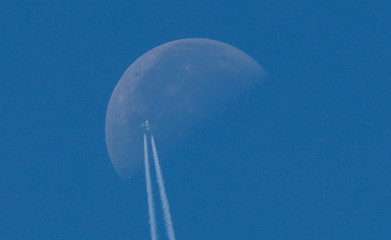 A passenger plane flies in the sky as the Moon is seen in Berlin