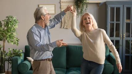Joyful active old retired romantic couple dancing in living room
