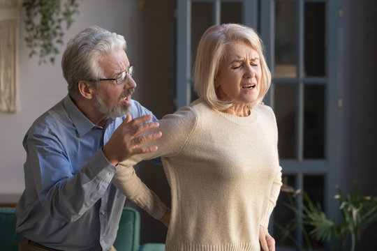 Senior husband helping middle aged wife feel sudden backpain