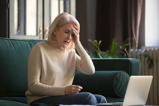 Tired upset mature woman feeling headache after computer work