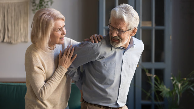 Worried mature wife supporting senior husband feel sudden back pain
