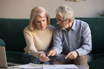 Serious stressed old couple looking at calculator feeling worried Fototapete