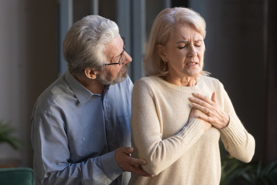 Worried elder husband helping wife touching chest having heart attack