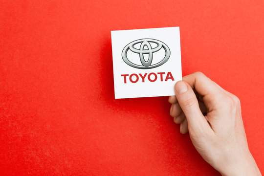LONDON, UK - October 26th 2018: Hand holding a Toyota logo. Toyota is an automobile manufacturer.