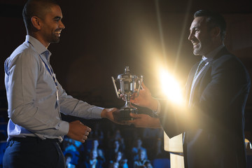 Businessman giving trophy to business male executive on stage in auditorium
