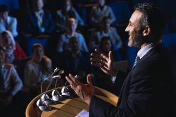 Businessman standing and giving presentation in the auditorium