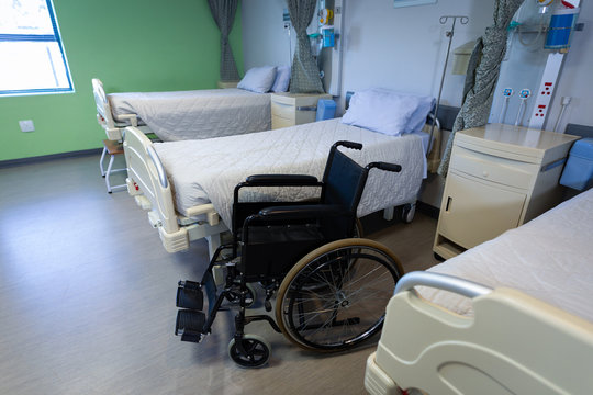 Row of empty hospital beds and wheelchair