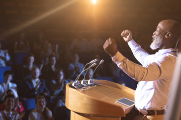 Businessman standing near podium and giving speech to the audience in the auditorium