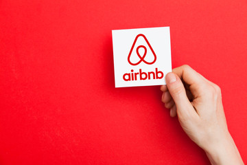 LONDON, UK - May 7th 2017: Hand holding Airbnb logo. Airbnb is a popular online home vacation rental company