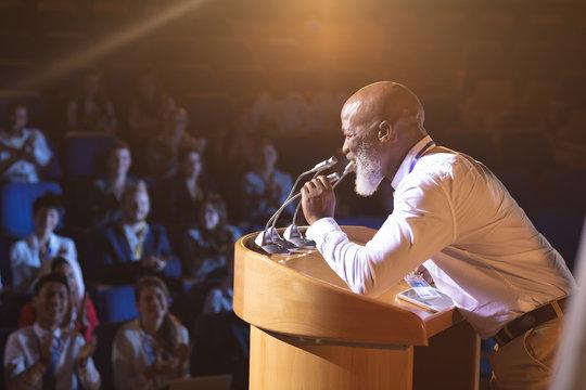 Businessman standing and holding speaker to speak in the auditorium