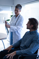Mature female doctor showing x-ray report to patient in clinic
